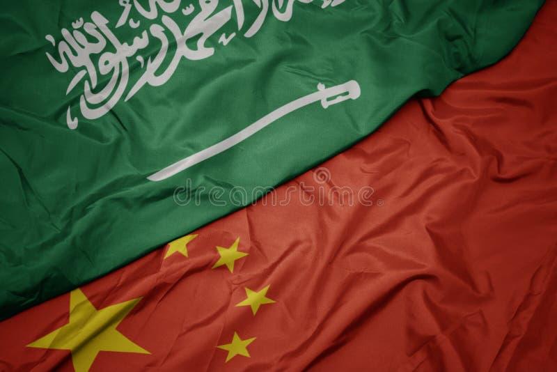golvende kleurrijke vlag van China en nationale vlag van Saudi-Arabië stock foto