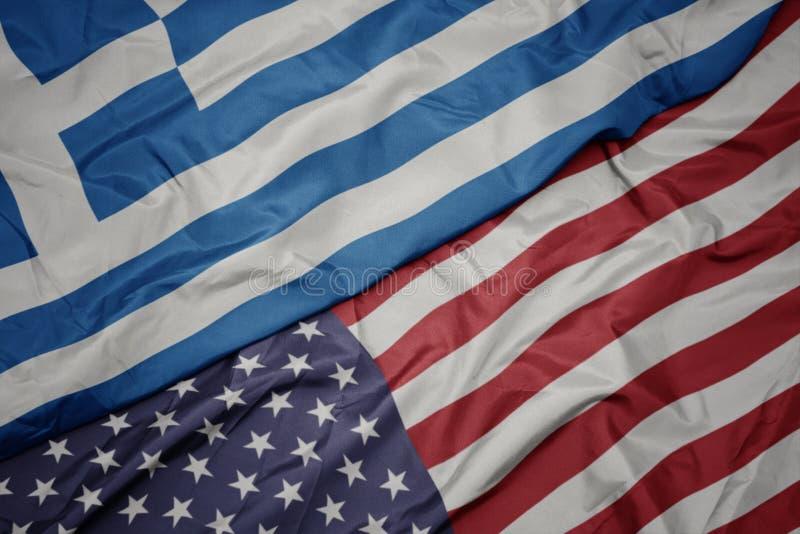 golvende kleurrijke vlag van de Verenigde Staten van Amerika en nationale vlag van Griekenland Macro stock afbeelding