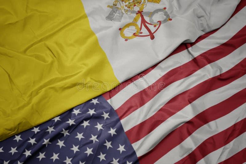 golvende kleurrijke vlag van de Verenigde Staten van Amerika en nationale vlag van de stad van Vatikaan Macro stock afbeeldingen