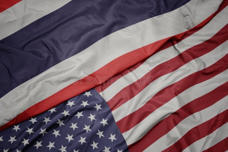 golvende kleurrijke vlag van de Verenigde Staten van Amerika en nationale vlag van Thailand stock fotografie