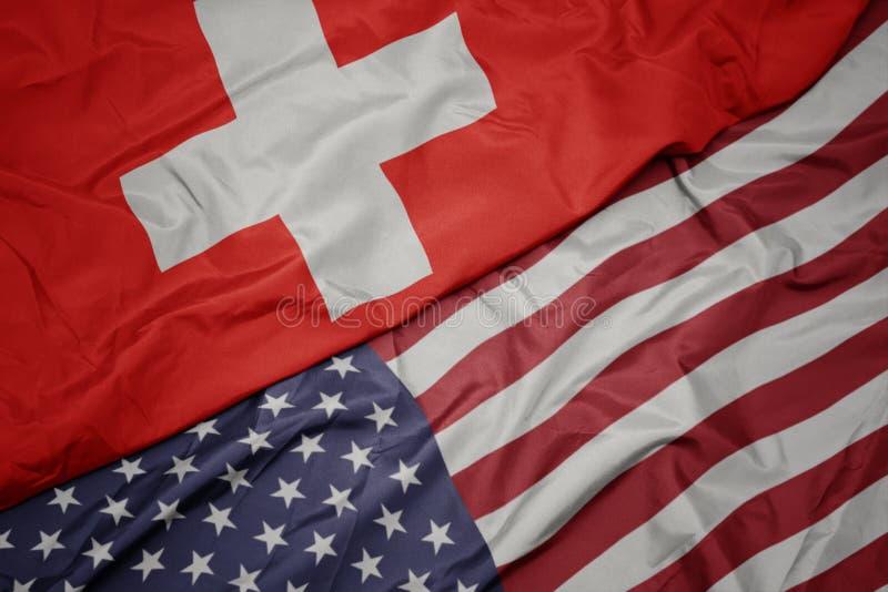 golvende kleurrijke vlag van de Verenigde Staten van Amerika en nationale vlag van Zwitserland Macro stock foto's