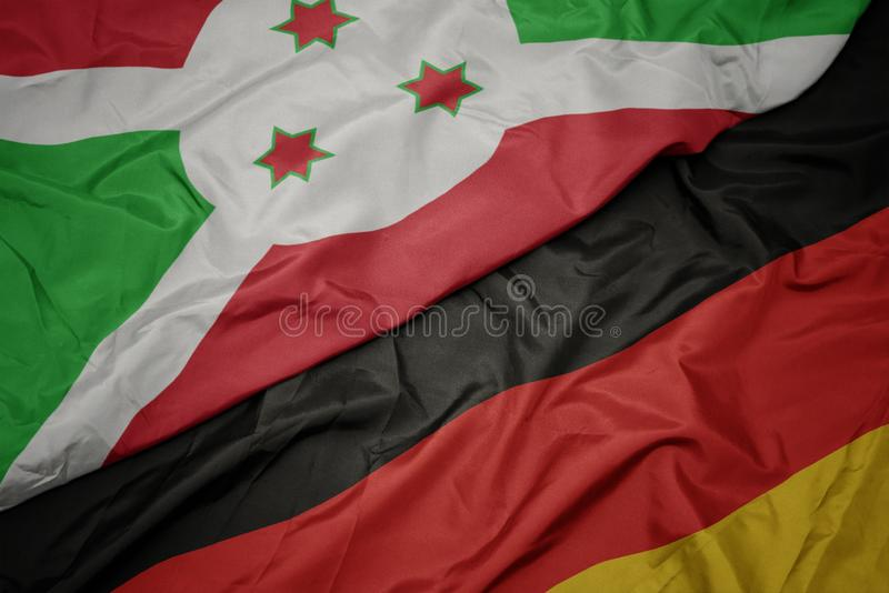 golvende kleurrijke vlag van Duitsland en nationale vlag van Burundi royalty-vrije stock foto's
