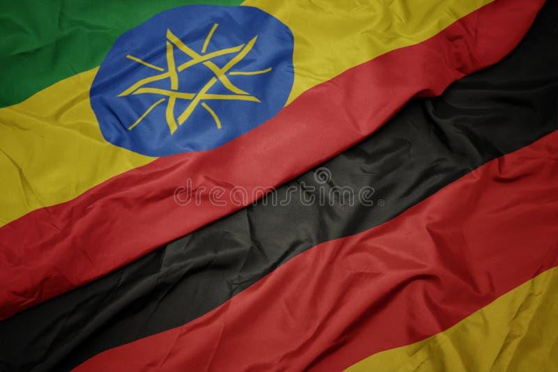 golvende kleurrijke vlag van Duitsland en nationale vlag van Ethiopië stock afbeelding