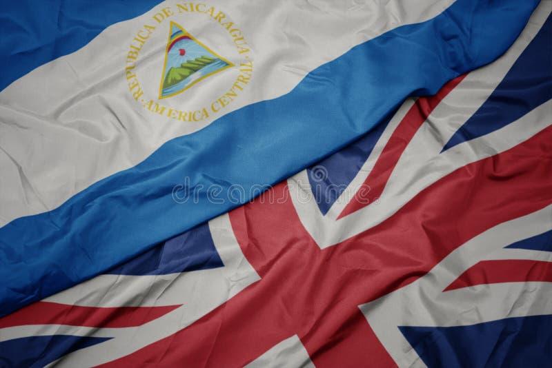 golvende kleurrijke vlag van Groot-Brittannië en nationale vlag van Nicaragua stock fotografie