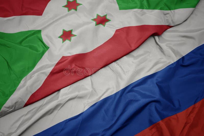 golvende kleurrijke vlag van Rusland en nationale vlag van Burundi royalty-vrije stock foto