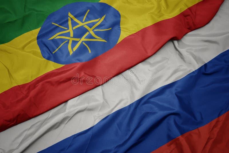 golvende kleurrijke vlag van Rusland en nationale vlag van Ethiopië royalty-vrije stock afbeelding