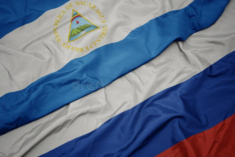 golvende kleurrijke vlag van Rusland en nationale vlag van Nicaragua stock foto