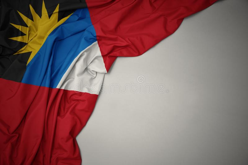 Golvende nationale vlag van antigua en Barbuda op een grijze achtergrond royalty-vrije stock afbeeldingen