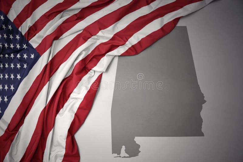 Golvende nationale vlag van de Verenigde Staten van Amerika op een grijze de kaartachtergrond van de staat van Alabama stock foto