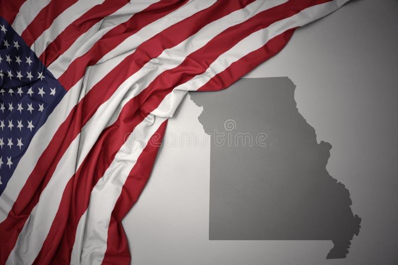 Golvende nationale vlag van de Verenigde Staten van Amerika op een grijze de kaartachtergrond van de staat van Missouri stock foto