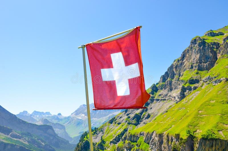 Golvende vlag van Zwitserland met het landschap van de de zomerberg op achtergrond Nationaal symbool Zwitserse Alpen Wit kruis op royalty-vrije stock afbeelding