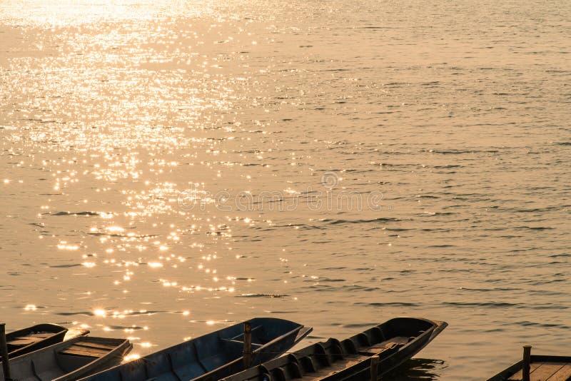 Golvende waterspiegel met schitterende oranje zonlicht en rij van boten die met lange staart op de kust parkeren royalty-vrije stock afbeelding