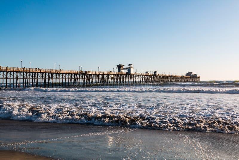 Golvenneerstorting op Strand met Oceanside-Visserijpijler stock afbeelding