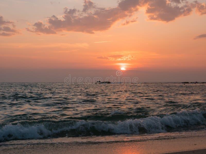 Golvenneerstorting op zandig strand bij zonsondergang met levendige oranje hemel stock afbeeldingen