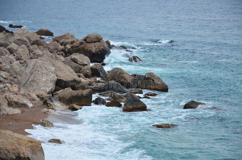 Golvenoverlapping tegen de rotsen stock foto