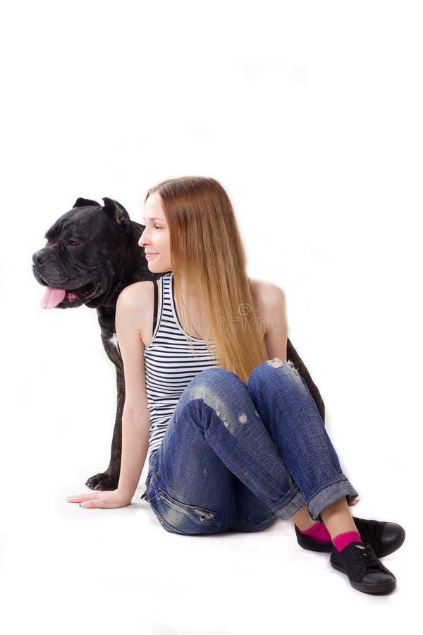 golvflickan sitter Hennes hundCane Corso sammanträde på henne Se i sidan royaltyfria bilder