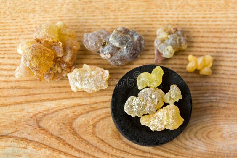Goma amarela aromática grande da resina no disco redondo preto do cha árabe imagens de stock royalty free