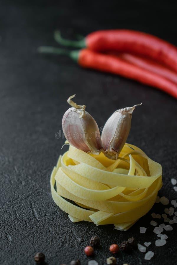Goma cruda del fettuccine con los clavos de ajo, el horno del chile y las especias fotografía de archivo libre de regalías