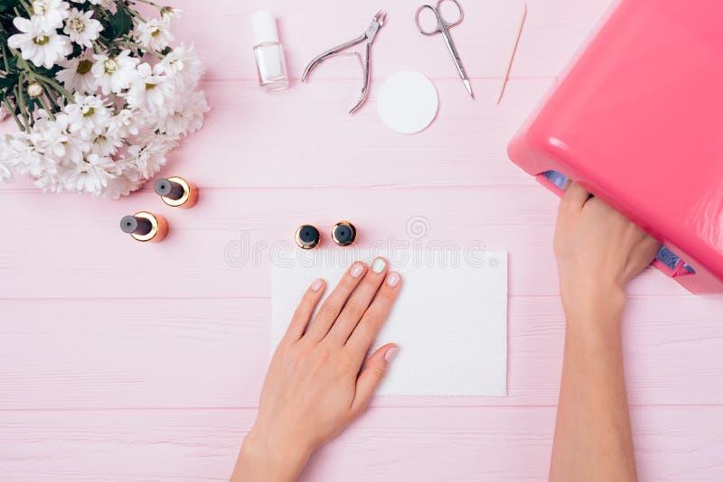 Goma-laca de polimerização da mão da mulher que cobre na lâmpada ultravioleta fotos de stock
