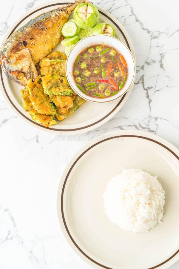 goma picante del camarón con los pescados fritos de la caballa, el huevo frito con el zarzo que sube y el arroz fotografía de archivo
