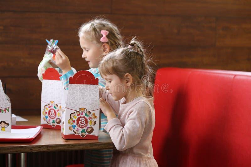 GOMEL BIAŁORUŚ, Październik, - 28, 2017: Dzieci w kawiarni otwierają jedzenie w prezenta pudełku fotografia royalty free