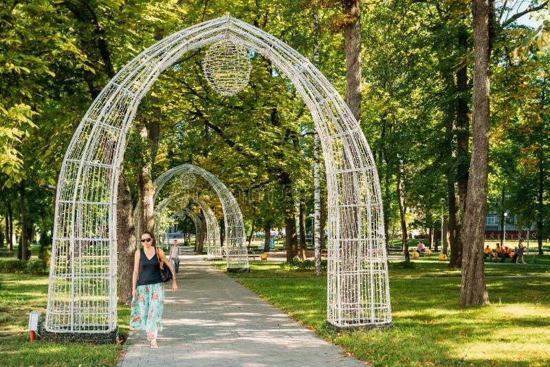Gomel, Bielorrússia Jovem mulher que passa através dos arcos decorativos fotos de stock