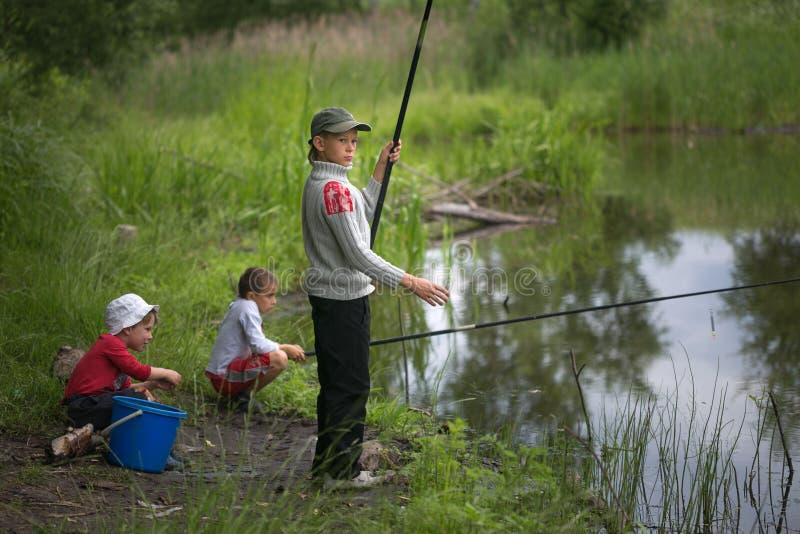 GOMEL VITRYSSLAND - Juni 25, 2017: Bybarn som fiskar på sjön med metspön arkivbild