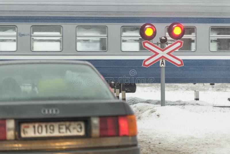 Gomel, Weißrussland - 25. Dezember 2016: Autos sind am Bahnübergang, und am geführten Zug lizenzfreies stockbild