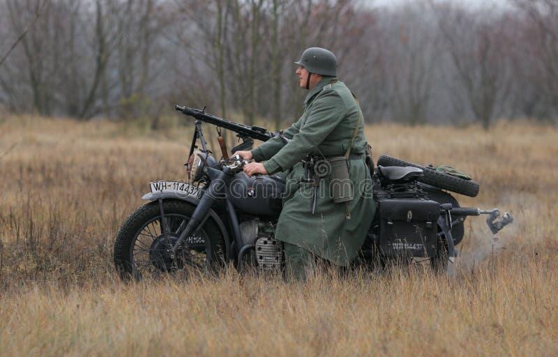 Gomel, Weißrussland - 26. November 2017: Wieder--enactors gekleidet als deutsche Soldaten in WW II kämpfen mit einer Kanone Feier lizenzfreie stockfotografie