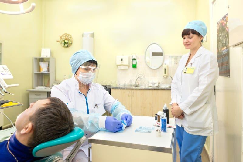 Gomel, Wit-Rusland - 22 Februari 2017: het tandarts` s bureau de verpleegster bereidt de geduldige toelating van ` s aan de arts  royalty-vrije stock foto