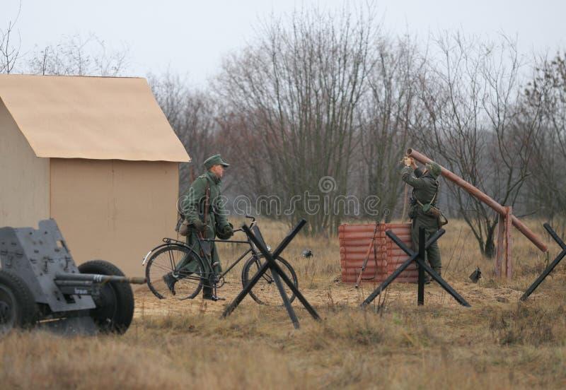 Gomel, Wit-Rusland - November 26, 2017: Re-Enactors kleedden zich aangezien de Duitse Militairen in WO.II met een Kanon vechten V stock foto