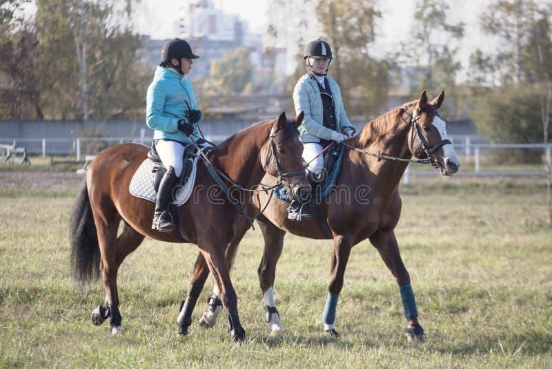 Gomel, Wit-Rusland - Oktober 16, 2016: De twee meisjesruiter warmt de paarden vóór de concurrentie op stock afbeelding