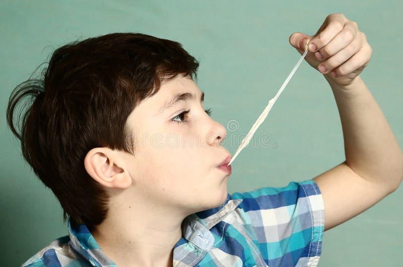 Gomma da masticare di tirata del ragazzo con la sua mano dal lepidottero fotografia stock