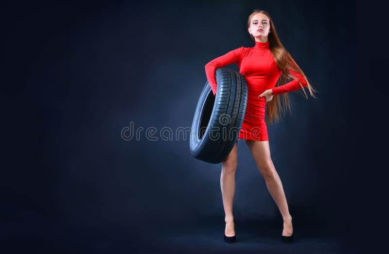 Gomma della tenuta della donna in sue mani Fondo delle gomme di automobile Insegna con lo spazio della copia immagini stock