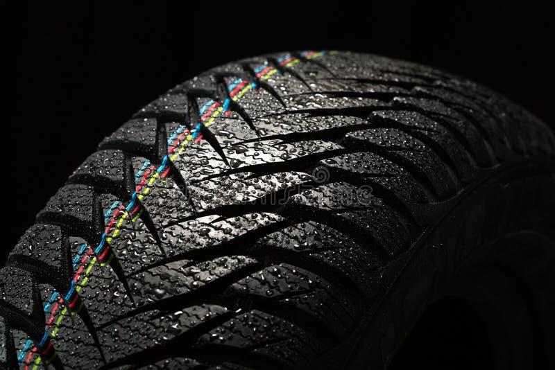 Gomma di automobile bagnata sul nero fotografia stock libera da diritti
