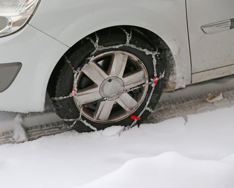 Gomma di automobile con le catene di neve nell'inverno fotografie stock