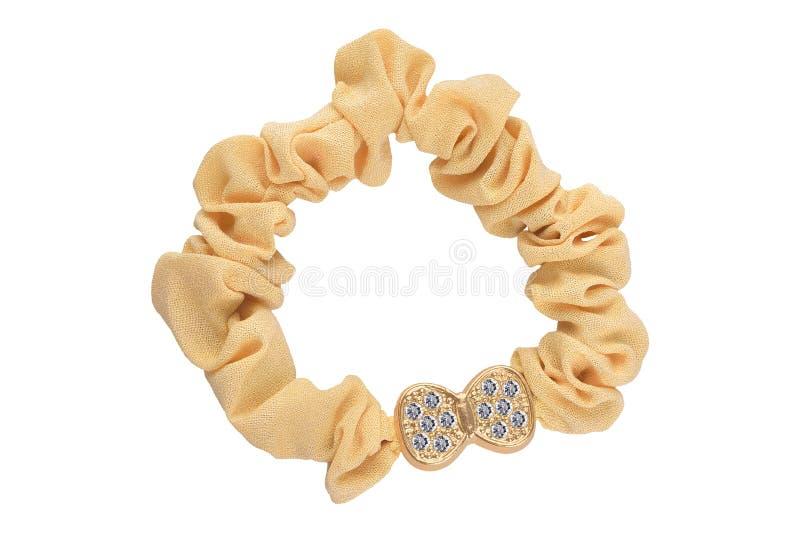 Gomma elastica dei capelli del tessuto beige scrunchy con la decorazione a forma di arco dorata e piccoli i diamanti, isolati su  immagine stock