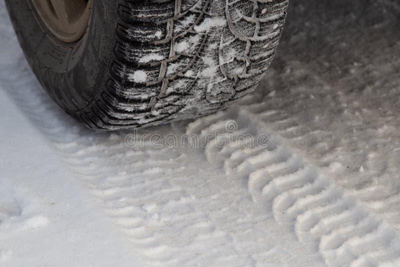 Gomma per l'inverno con le punte e la sua impronta sulla strada fotografia stock libera da diritti