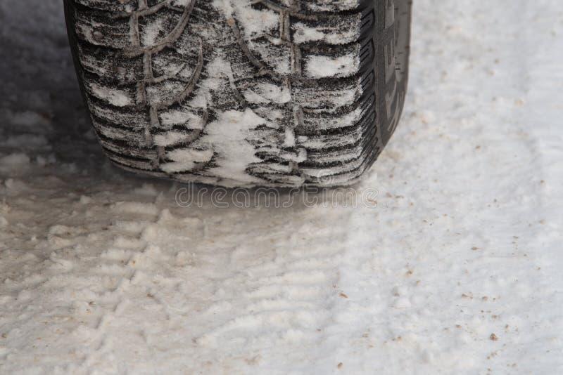 Gomma per l'inverno e la sua impronta sulla strada coperta di neve fotografie stock libere da diritti