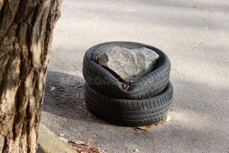 Gomme di auto usata impilate sopra a vicenda sulla strada al bordo Ostacolo per parcheggio spontaneo fotografie stock libere da diritti