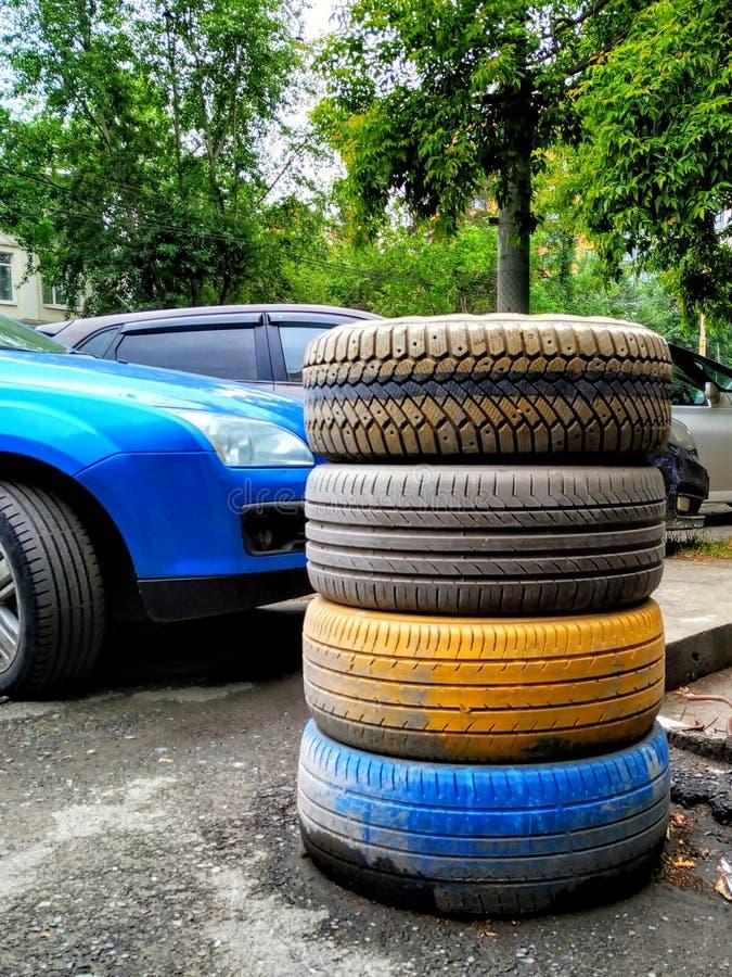 Gomme di automobile impilate sopra a vicenda Dipinto in giallo ed in blu fotografia stock libera da diritti