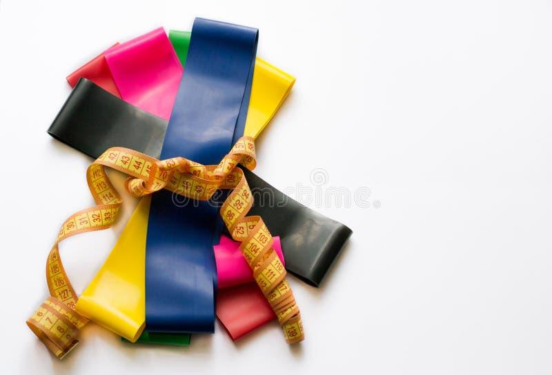 Gommes colorées de forme physique attachées avec la bande de mètre d'isolement sur le fond blanc Concept de sport - extenseurs él images libres de droits