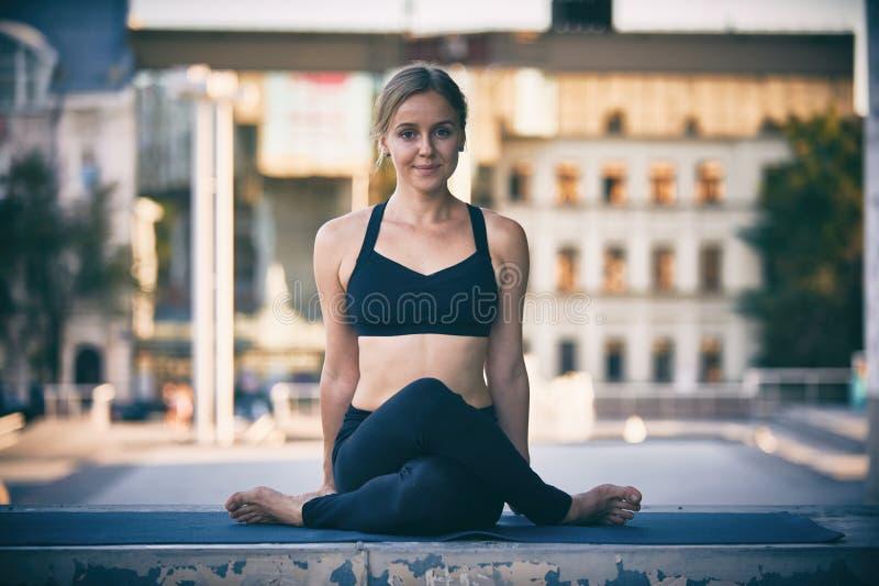 Gomukhasana hermoso de la actitud de la cara de la vaca del asana de la yoga de las prácticas de la mujer joven en la ciudad imagen de archivo