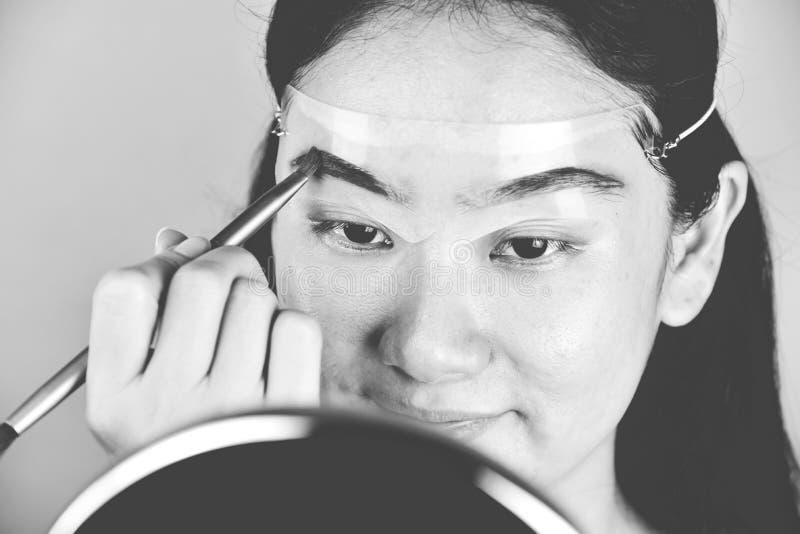?gonbryn som formar makeupmallen, asiatiska kvinnor som fyller ?gonbryn f?r att se mer tjock royaltyfria bilder
