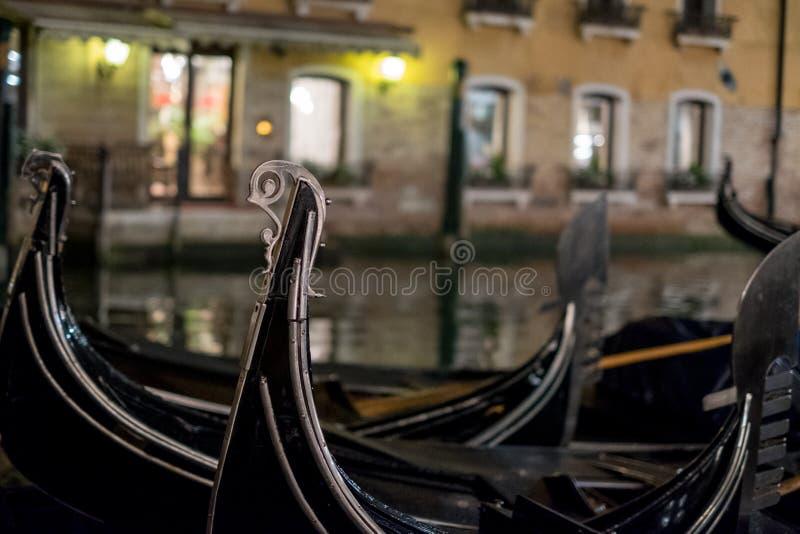 Gondalas在一条运河停放了在威尼斯,显示装饰耶老岛/铁的意大利在小船和risso的弓 免版税库存照片