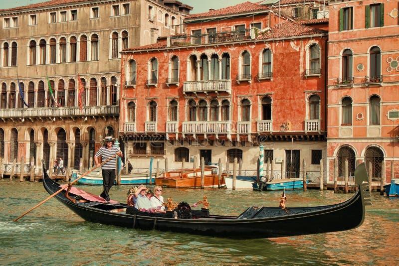 Gondel, die Touristen für Fahrt in Venedig nimmt lizenzfreie stockfotos