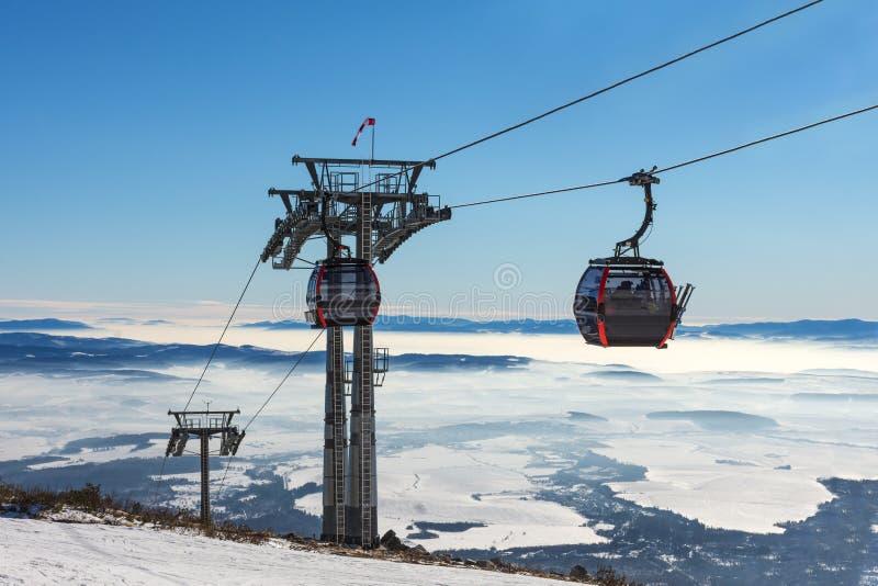 GONDELBAHN Kabine des Skiliftes im Skiort am frühen Morgen an der Dämmerung mit Bergspitze im Abstand stockfotografie