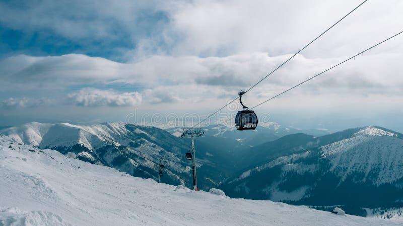 GONDELlift Cabine van skilift in de skitoevlucht Yasna bij dageraad met bergpiek in de afstand De winter snowboard en ski?end stock afbeelding