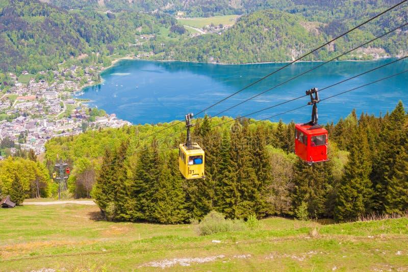 Gondeln der Kabelweise Zwoelferhorn Seilbahn und der Ansicht der alpinen Stadt StGilgen und des Wolfgangsee Sees stockfotografie