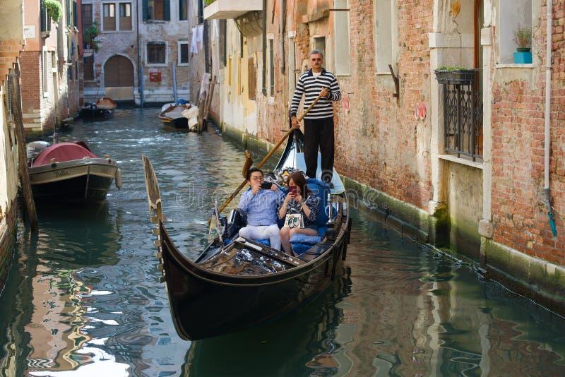 Gondol med kinesiska turister på stadskanalen italy venice royaltyfri foto
